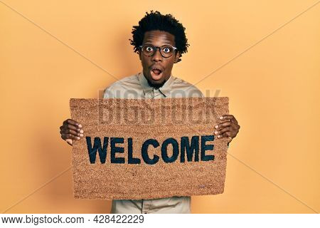 Young african american man holding welcome doormat afraid and shocked with surprise and amazed expression, fear and excited face.