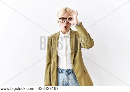 Beautiful caucasian business woman standing over isolated background doing ok gesture shocked with surprised face, eye looking through fingers. unbelieving expression.