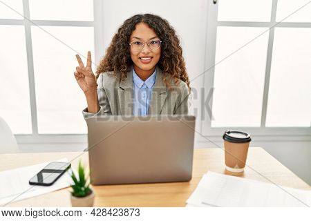 Beautiful hispanic business woman sitting on desk at office working with laptop smiling with happy face winking at the camera doing victory sign. number two.