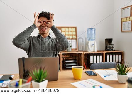 Young hispanic man wearing business style sitting on desk at office doing ok gesture like binoculars sticking tongue out, eyes looking through fingers. crazy expression.