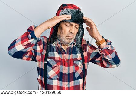 Handsome mature man wearing winter hat with ear flaps suffering from headache desperate and stressed because pain and migraine. hands on head.
