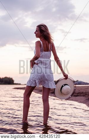 A Woman Holds A Straw Hat In Her Hands. A Beautiful Happy Blonde In A White Summer Dress Holds The H