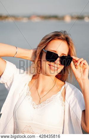 A Young Woman In Sunglasses At Dawn. Portrait Of A Beautiful Young Blonde In A White Dress And Shirt