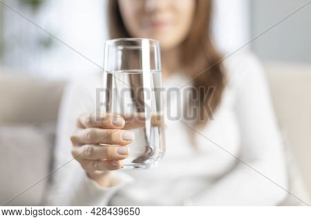 Young Woman Drinking Water Sitting On A Couch At Home. Health Benefits Of Drinking Enough Water Conc
