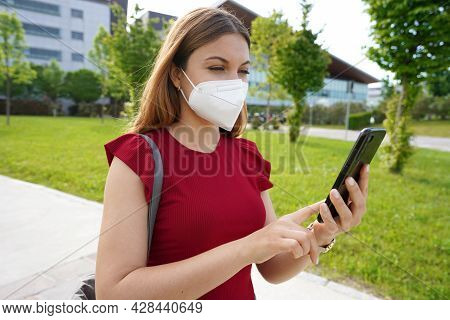 Citizen Female With Medical Mask Watching Her Mobile Phone Outdoor. Green Pass And Digital Covid Cer