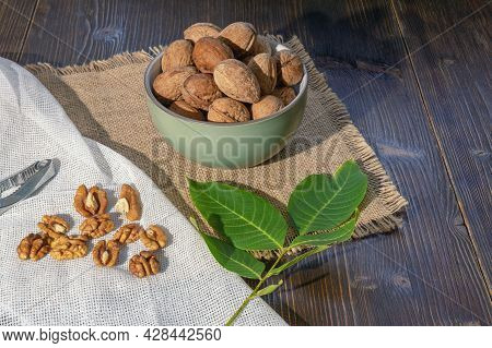 Whole Walnuts And Kernels On Dark Rustic Table.  Leaves Of Walnut Tree.  Copy Space