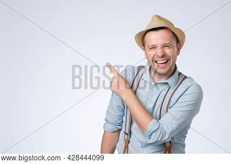 Happy Young Man In Hat Pointing Aside With Forefinger On Copyspace.