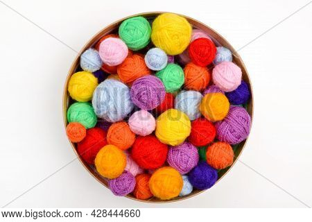 A Lot Of Colorful,woolen Balls Of Knitted Yarn In A Round Cardboard Box On A White Background.the Co