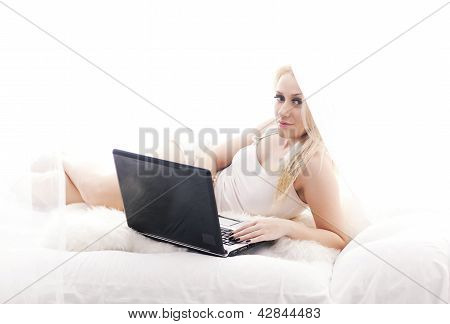 Blonde Girl With Laptop Lying In Bed