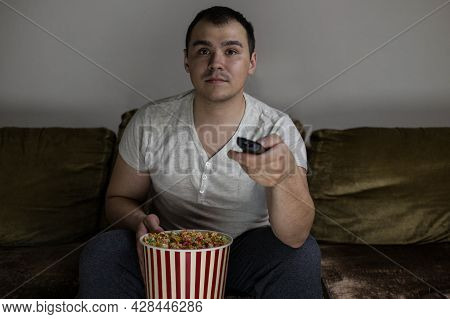 A Man At Home In The Evening On The Couch With Popcorn And A Remote Control, Enthusiastically Watchi