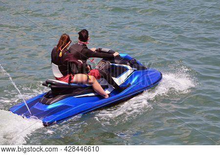 Young Couple Riding Tandem On A Blue Jetski.