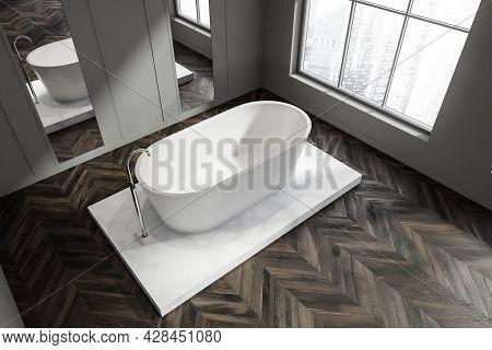 Top View Of A Corner Minimalist Bathroom Interior With Dark Parquet Flooring, Gray Walls With Mirror
