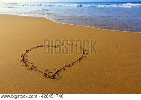 Heart sign in the sand on the ocean coast