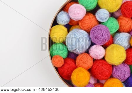A Lot Of Colorful Wool Balls Of Knitted Yarn In A Round Cardboard Box On A White Background.the Conc