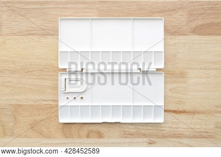 White Watercolor Palette. Empty Watercolor Tray Isolated On Wood Background.