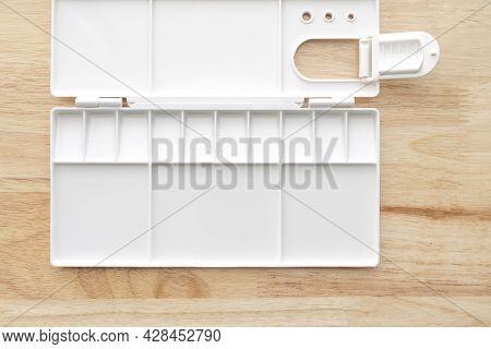 Empty Watercolor Palette Background. White Plastic Paint Palette. Watercolor Tray On Wood Background