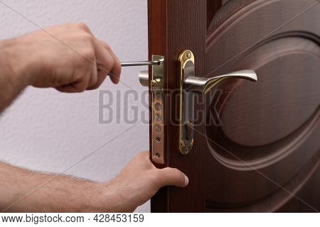 Handyman With Screwdriver Repairing Door Lock, Closeup