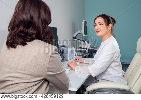 Female Doctor Listens To Complaints Of Female Patient, Taking Anamnesis.