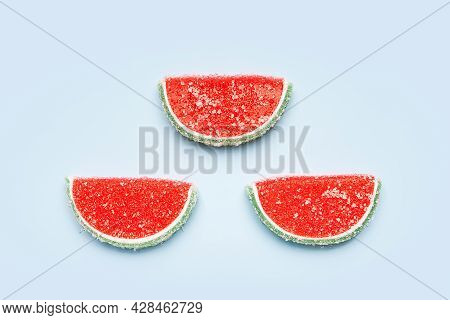 Jelly Candies. Top View Of Three Watermelon Jelly Candies Sprinkled With Sugar On A Blue Background.