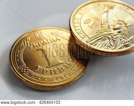 Translation: Ukraine, Hryvnia. Ukrainian Coin In 1 Hryvnia And Us One In One Dollar. Hang Over A Whi