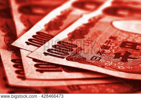 Close-up Of Several Japanese 1,000 Yen Bills. Dramatic Red Tinted Illustration. Money, Finance, Book