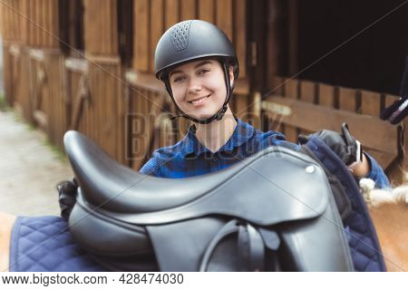 Female Jockey Standing With Her Horse Outside The Horse Stable. The Jockey Is Ready For The Horse Ri