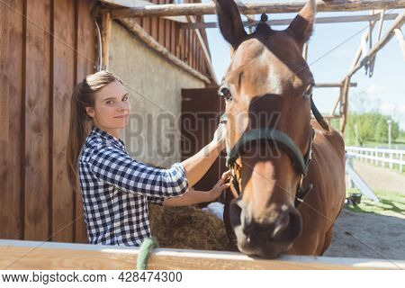 Female Horse Rider With Her Dark Bay Horse In The Stable During The Daytime. The Girl Is Smiling And