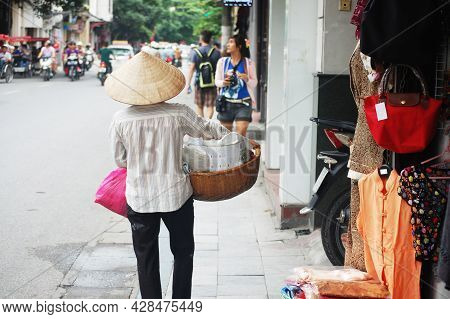 Vietnam Woman Vendors Bearing Hawker Basket Walking On Street Road For Sale Local Food Product To Vi