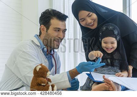 Health Care Concept. Muslim Mother Wear Hijab With Own Little Daughter Visit Professional Doctor Man