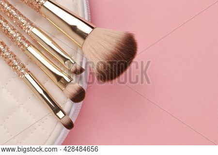 A Golden Set Of Makeup Brushes On A White Cosmetic Bag.professional Makeup Artist Tools For Applying