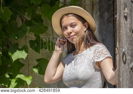 A Young Girl Of 17-20 Years Old In A White Dress And A Straw Hat Smiles And Opens A Wooden Door, Lea
