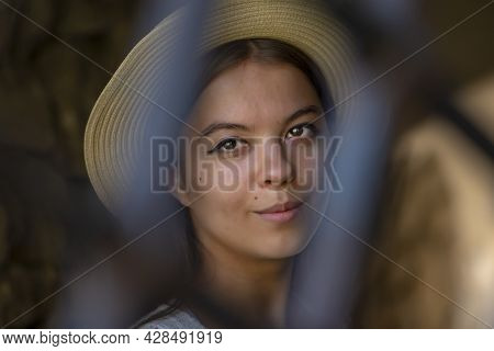 A Young Girl Of 17-20 Years Old In A Straw Hat Looks Through Metal Bars, Selective Focus, Close-up.
