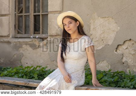 Portrait Of A Young Girl 17-20 Years Old In A Straw Hat And White Dress Sitting On A Wooden Bench Ne