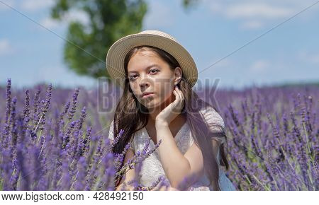 Street Portrait Of A Serious Young Girl 17-20 Years Old In A White Dress And Straw Hat With Long Bla