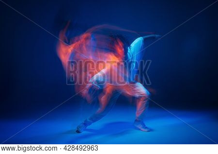 Mixed Race Young Girl Dancing In Colorful Neon Studio Light. Long Exposure. Contemporary Hip Hop Dan