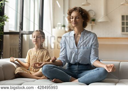 Peaceful Mother With Little Daughter Meditating On Couch Together