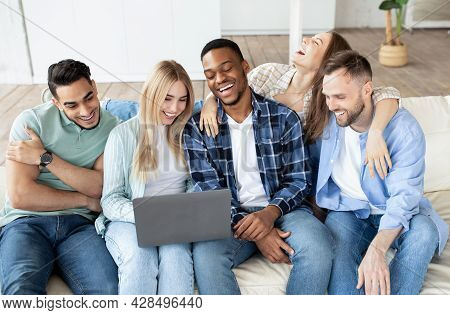 Happy Multiethnic Friends Using Laptop Computer, Sitting On Couch, Watching Movie, Having Video Call