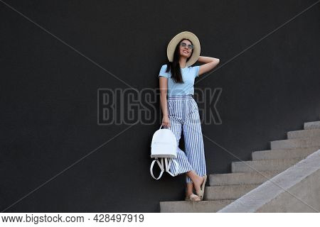 Beautiful Young Woman With Stylish Backpack And Hat On Stairs Leaning To Black Wall