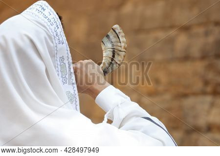 Jewish Man Blowing Shofar On Rosh Hashanah Outdoors. Wearing Tallit With Words Blessed Are You, Lord