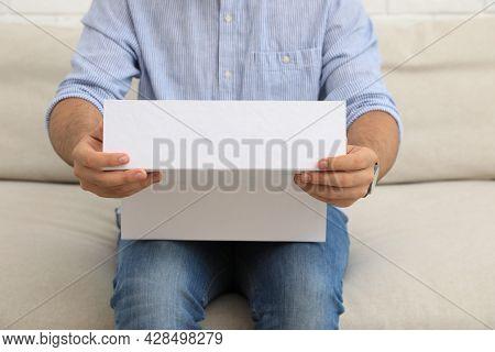 Man Unpacking Parcel At Home, Closeup. Online Shopping