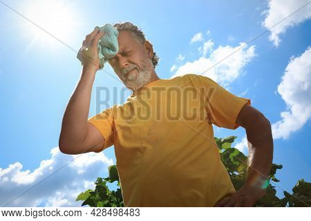 Senior Man With Towel Suffering From Heat Stroke Outdoors, Low Angle View