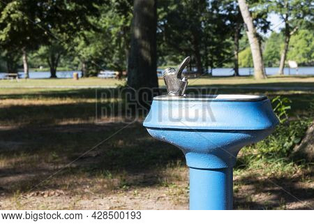 Top Of A Blue Water Fountain In Belmont Lake State Park Long Island New York.