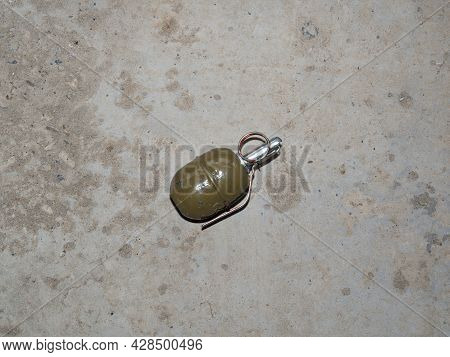 A Green Hand-held Offensive Grenade Lies On Its Side On The Gray Concrete Floor. The Concept Of Defu