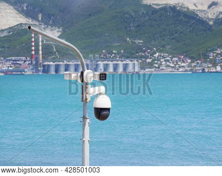 Many Street Surveillance Cameras Hang On A Pole Against The Background Of The Sea. A Video Monitorin