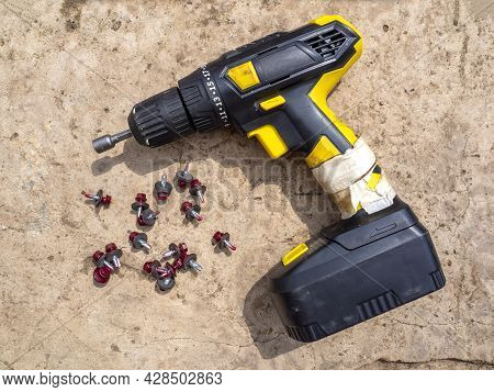 Black And Yellow Cordless Screwdriver Lies On The Gray Concrete Floor Next To The Crimson Short Roof