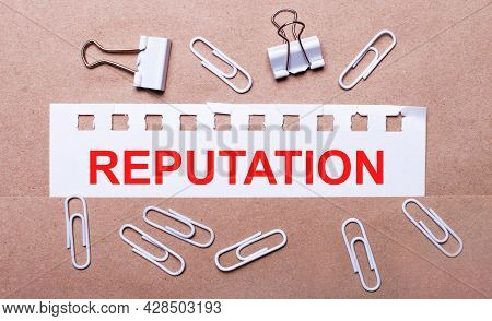 On A Brown Background, White Paper Clips And A Torn Strip Of White Paper With The Text Reputation