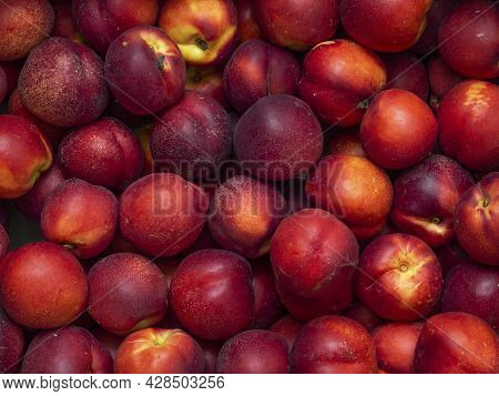 Background Of Bright And Ripe Nectarines In Full Screen. Autumn Wallpaper Of Exotic Southern Fruits.