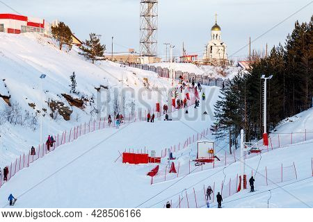 A Ski Slope For Beginners With A Lot Of People On It And A Fence, A Chapel And Trees On Top Of The S