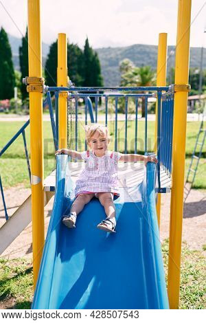 Little Girl Sitting On A Slide In The Playground, Getting Ready To Slide Down