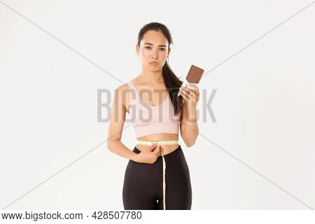 Sport, Wellbeing And Active Lifestyle Concept. Disappointed Gloomy Asian Girl Measuring Waist With T